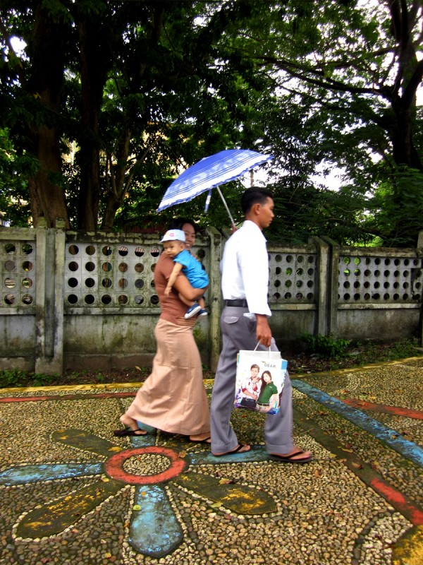 Burmese family on colorful sidewalk in Yangon, Myanmar