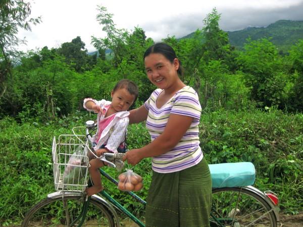 Burmese mother and child bicycling, Inle Lake, Myanmar