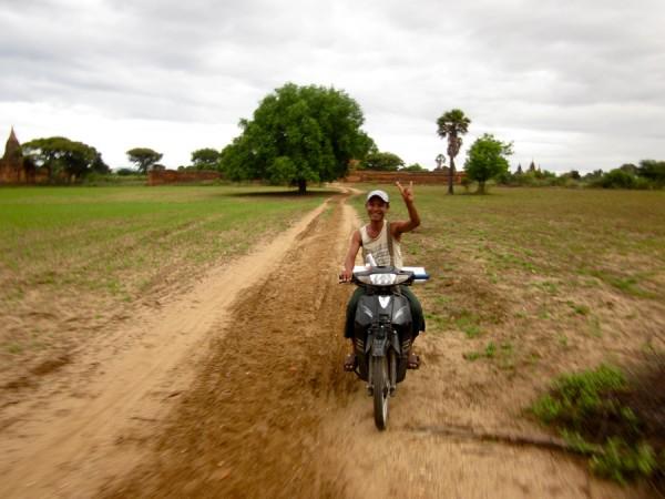 Burmese man on motorbike at Bagan pagodas, Myanmar